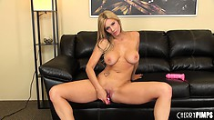 She sits back down after posing and starts toying her bald pussy